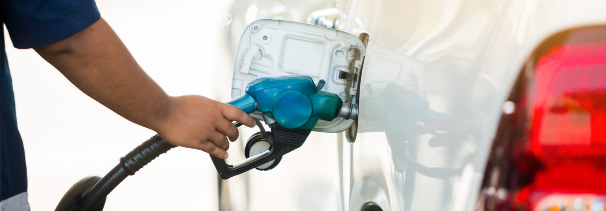 Hand refilling the white pickup truck with fuel at the gas station. Oil and